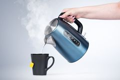 Female hand pours hot water from an electric kettle into a black mug, on light background. Female hand pours hot water from an electric kettle into a black mug royalty free stock images