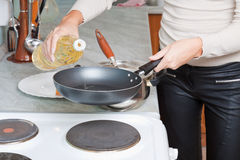 Female hand pours oil on frying pan Royalty Free Stock Photos