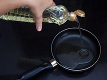 Female hand pours vegetable oil on a frying pan Royalty Free Stock Images