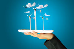 Female hand present wind turbine power generator Royalty Free Stock Photography