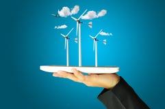 Female hand present wind turbine power generator Royalty Free Stock Photography