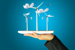 Female hand present wind turbine power generator. Female hand holding a tablet touch computer gadget present wind turbine power generator Royalty Free Stock Images