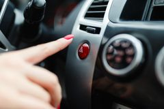 The female hand presses the button to turn the alarm into the car. Button emergency car lighting shot of a finger. Woman finger pressing emergency button on royalty free stock image