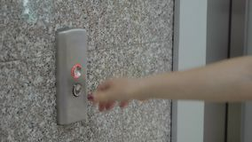 Female hand presses the elevator call button stock footage
