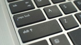 Female hand pressing caps lock button on keyboard to make typing letters capital