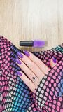 Female hand with purple long nails and nail polish bottle. Female hand with purple long nails manicure and nail polish bottle royalty free stock image