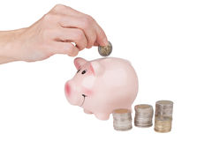 Female hand puts a coin in the piggy bank Royalty Free Stock Photos