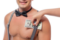 Female hand puts dollars under the strap suspenders Stock Image