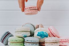 Female hand puts macaroons in a pile of almond cookies on a white wooden background, copy space. Female hand puts macaroons in a pile of almond cookies on a Stock Images