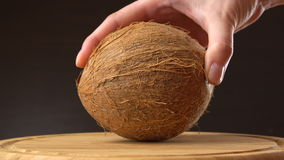 Female hand puts ripe tropical coconut on a wooden table against black background. Tropical fruit. Female hand puts ripe tropical coconut on a wooden table stock video