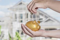 Female hand putting coin into a gold piggy bank with house construction background. Female hand putting coin into a gold piggy bank with house construction Stock Image