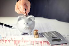 Female hand putting coin in piggy bank on the office desk Royalty Free Stock Photography