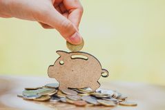 Female hand putting coin and stack of coins in concept of savings and money growing or energy save. stock images