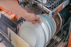 Female hand is putting dirty dish in dishwasher Royalty Free Stock Photography