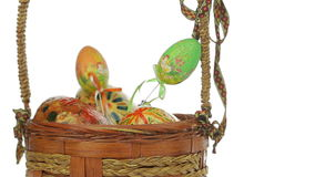 Female hand putting easter eggs in the basket stock video
