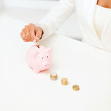 Female hand putting euro coins into piggy bank Royalty Free Stock Image