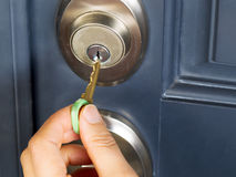Female hand putting house key into door lock. Photo of female hand putting house key into front door lock of house stock photo