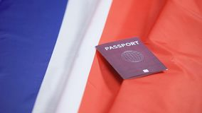 Female hand putting international red passport on french flag, citizenship. Stock footage stock video footage