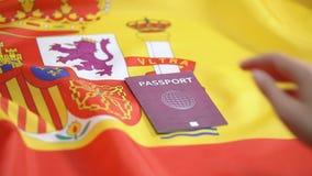 Female hand putting international red passport on Spanish flag, citizenship. Stock footage stock video