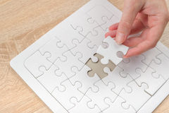 Female hand putting a missing piece into jigsaw puzzle Stock Photo
