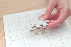 Female hand putting a missing piece into jigsaw puzzle Royalty Free Stock Photos
