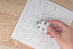 Female hand putting a missing piece into jigsaw puzzle Royalty Free Stock Photography