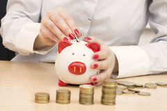 Female hand putting money coin into piggybank slot. Woman putting coin into piggy bank. Stacks of coins on the table. Making savings concept Royalty Free Stock Photo