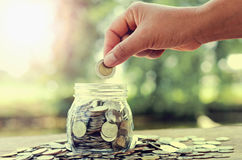 Female hand putting money coins in glass jar  concept saving for Royalty Free Stock Photos
