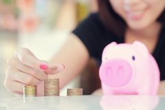 Female hand putting money into piggy bank. Royalty Free Stock Images
