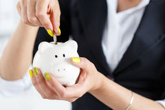 Female hand putting pin money coins. Into white piggybank slot. Budgeting expenses concept. Making savings and effective investment concept. Future needs Stock Image