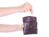 Female hand putting Polish Zloty coin into purse Royalty Free Stock Photo
