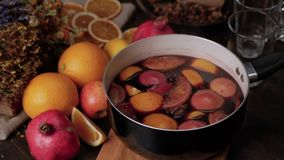 Female hand putting a saucepan of hot mulled wine on cutting board. Fresh lemons, oranges, pomegranate and dried herbs