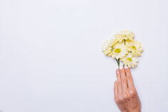 Female hand putting on white table yellow flowers. Top view Royalty Free Stock Images