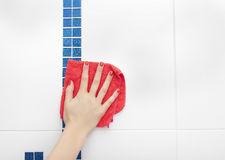 Female hand a rag washes the tile. Stock Photos