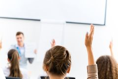 Female hand raised in class Royalty Free Stock Image