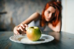 Female hand reaches plate with apple. Weight loss concept, fat burning, hard dieting Royalty Free Stock Image