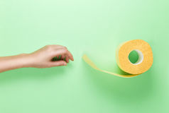 Female Hand Reaches for Yellow Toilet Roll on Green Background. Flat lay. Hygiene Glamour concept. Top View. Stock Image