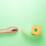 Female Hand Reaches for Yellow Toilet Roll on Green Background. Flat lay. Hygiene Glamour concept. Top View. Place  text Stock Image
