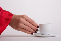 Female hand reaching for cup of espresso. Female hand is reaching out for a white cup with espresso in the morning Royalty Free Stock Image
