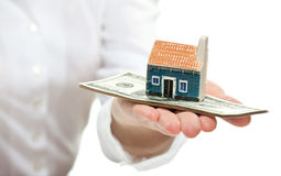 Female hand reaching out little house model to you Royalty Free Stock Photo
