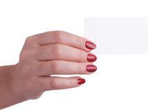 Female hand with red manicure holding a business card Royalty Free Stock Image