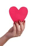 Female hand with red manicure holding a paper heart. Isolated on white background royalty free stock photography