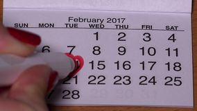 Female hand with red marker draw a heart shape in calendar february 14th. Holiday of love in 2017 year. 4K stock video footage