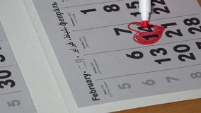 Female hand with red marker paint heart shape in the calendar february 14th stock video
