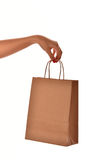 A female hand with red nail hold a paper shopping bag at the stu Stock Photos