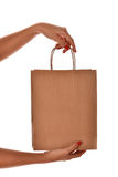 A female hand with red nail hold a paper shopping bag at the stu Royalty Free Stock Image