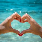Female hand with red nail in shape of heart against the background of sea. Love summer concept stock image