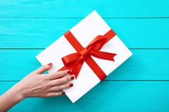 Female hand with red nails on gift box on blue wooden background. Top view and copy space. Mother day. Valentine and Christmas royalty free stock image