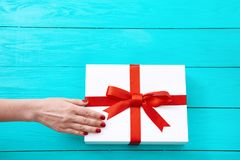 Female hand with red nails on gift box on blue wooden background. Top view and copy space. Mother day. Female hand with red nails on gift box on blue wooden stock photos