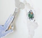 Female hand repairs wall Royalty Free Stock Image
